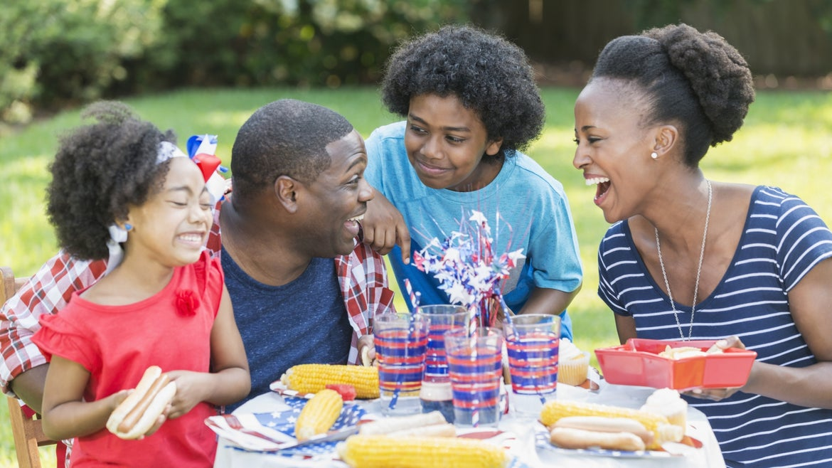 A family enjoying a backyard cookout on the 4th or July or Memorial Day.