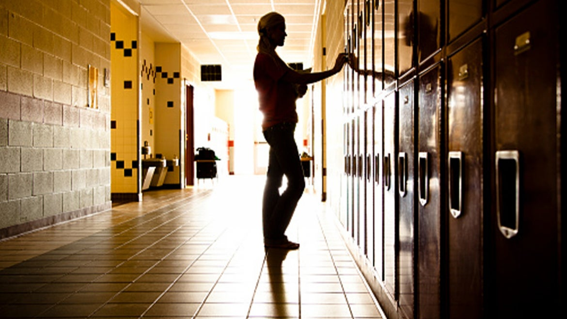 A silhouette of a student in a hallway.