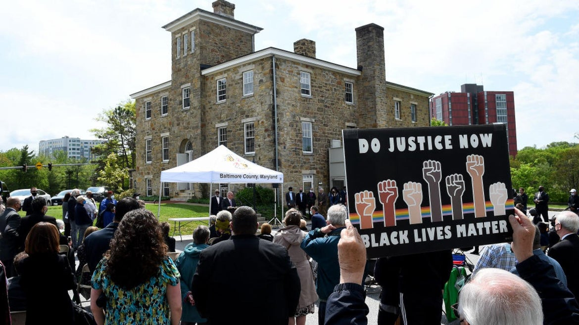 A Black Lives Matter sign is held while Maryland Governor Larry Hogan speaks during an event held by The Maryland Lynching Memorial Project at the old Baltimore County Jail in Towson, MD on May 8, 2021.