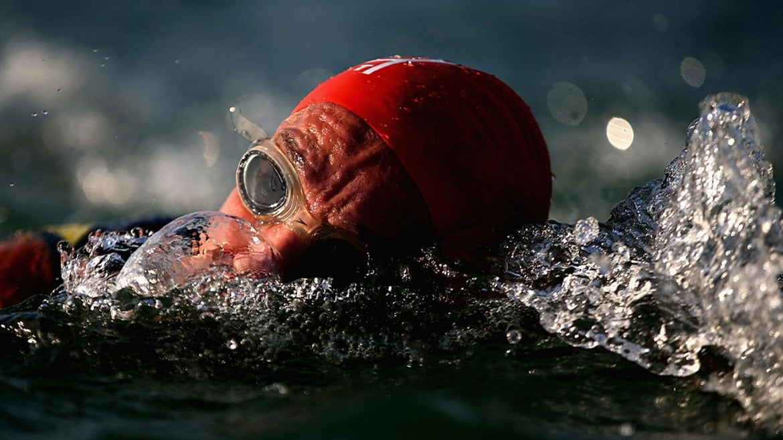 Stock image of athlete swimming in triathlon.