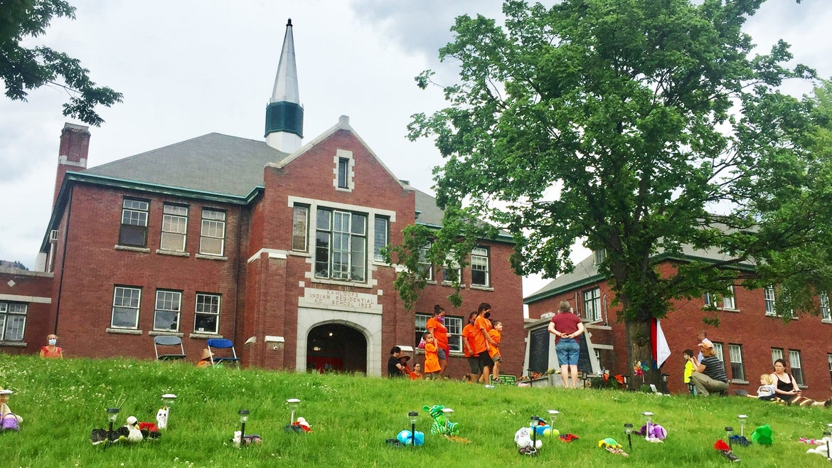Stuffed animals were placed in front of the former Kamloops Residential School Monday in a community vigil that encouraged attendees to wear orange, a Canadian tradition that aims to raise awareness for the atrocities of residential schools.