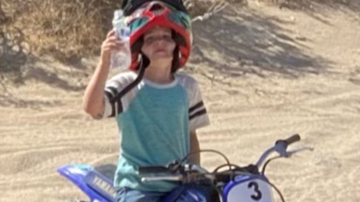 Dhal sitting on blue dirt bike with red helmet on