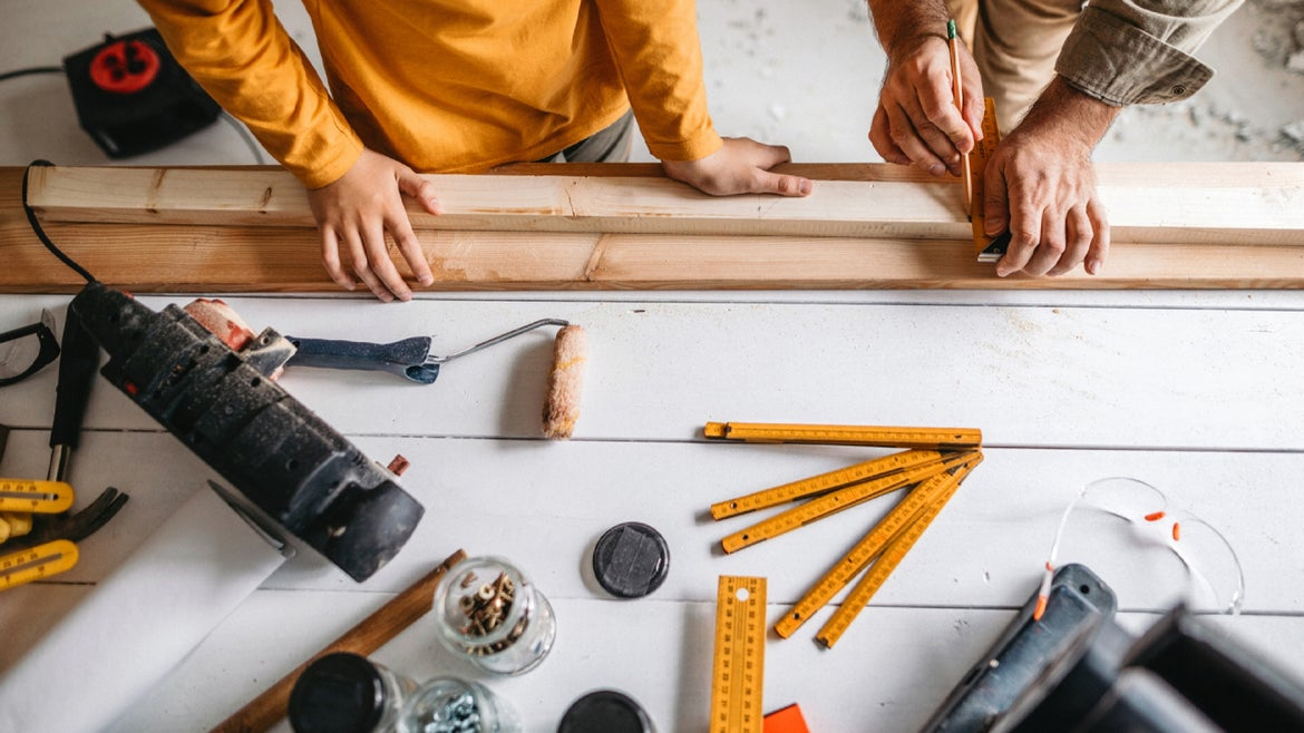 Photo of father with his son making measurements on a plank of wood
