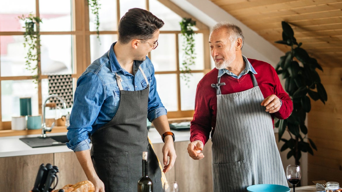 Senior father and his adult son preparing dinner together, father giving his son some advice about preparation.