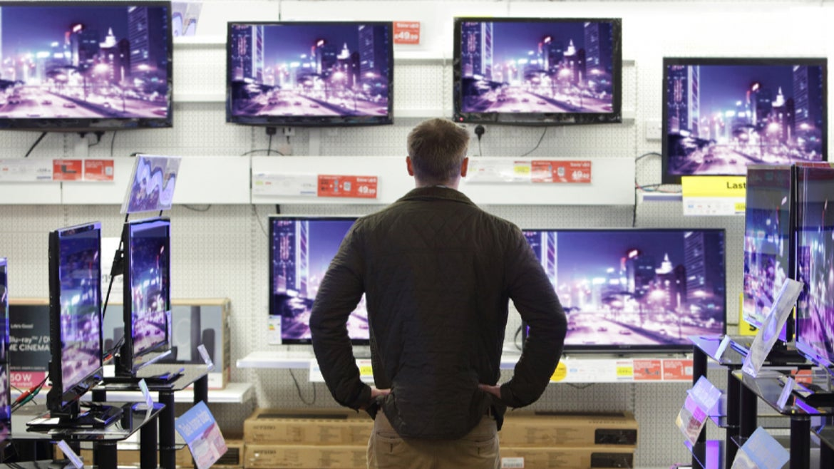 Man in front of TV sets