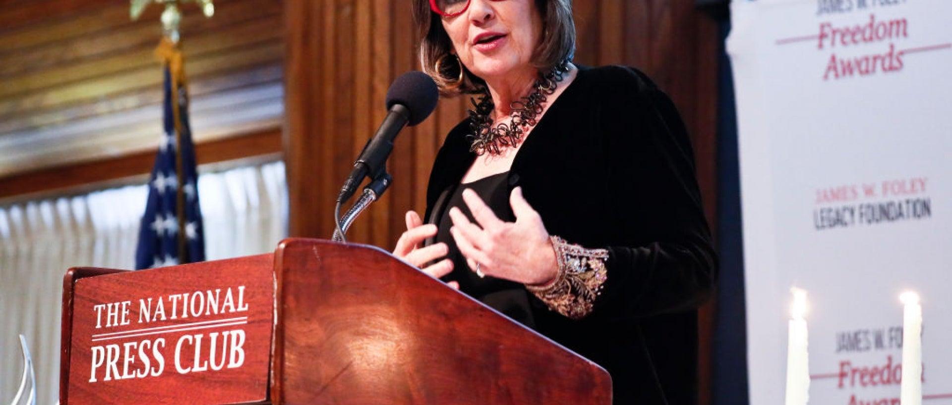 Christiane Amanpour standing at podium speaking