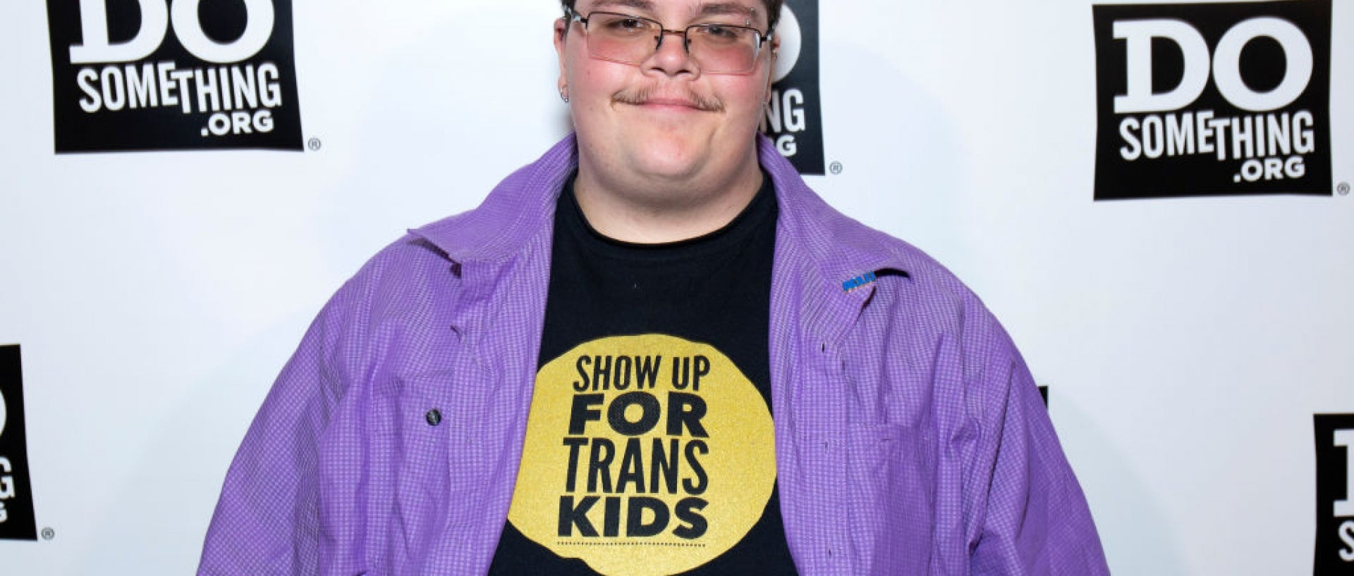 Gavin Grimm picture in front of a Do Something backdrop in a shirt that says Show Up For Trans Kids