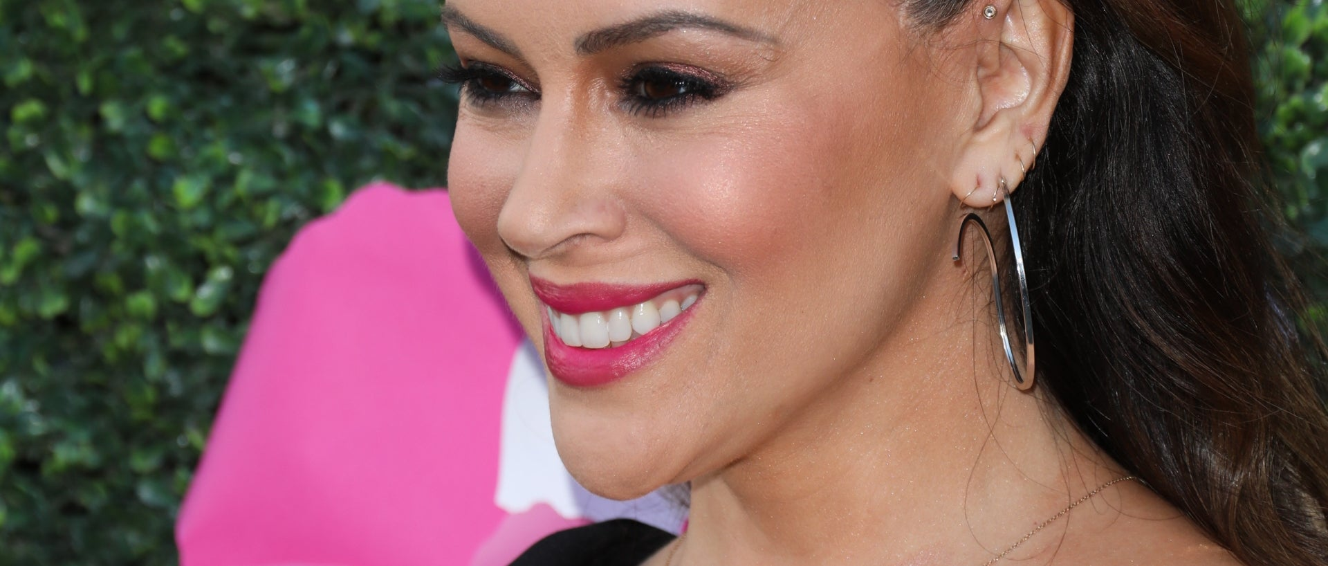 Alyssa Milano pictured with high pony, in black dress, smiling