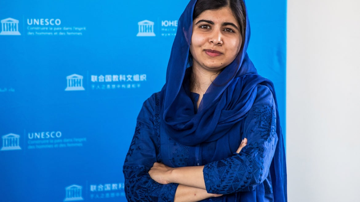 Malala Yousafzai standing for photo in blue outfit