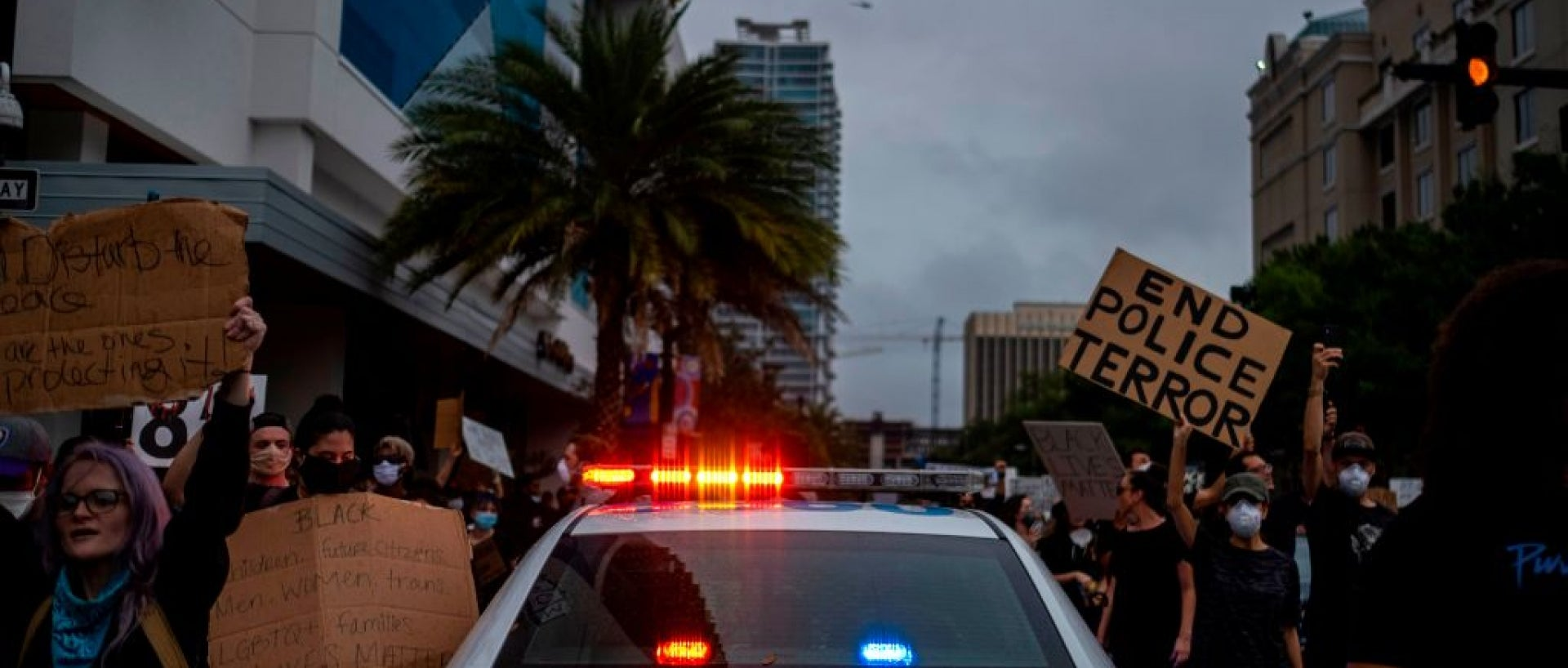 Image of police car driving through crowd of protestors against police brutality