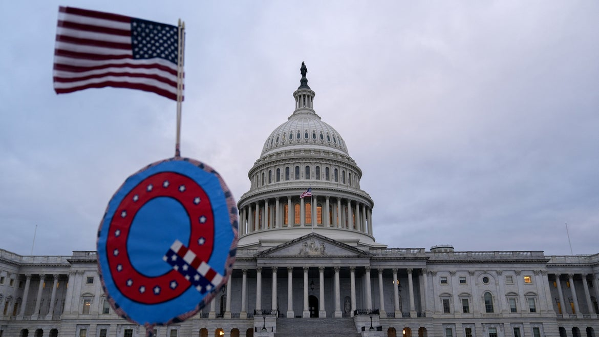 """A demonstrator holds a """"Q"""" sign outside the U.S. Capitol in Washington, D.C., U.S., on Wednesday, Jan. 6, 2021"""
