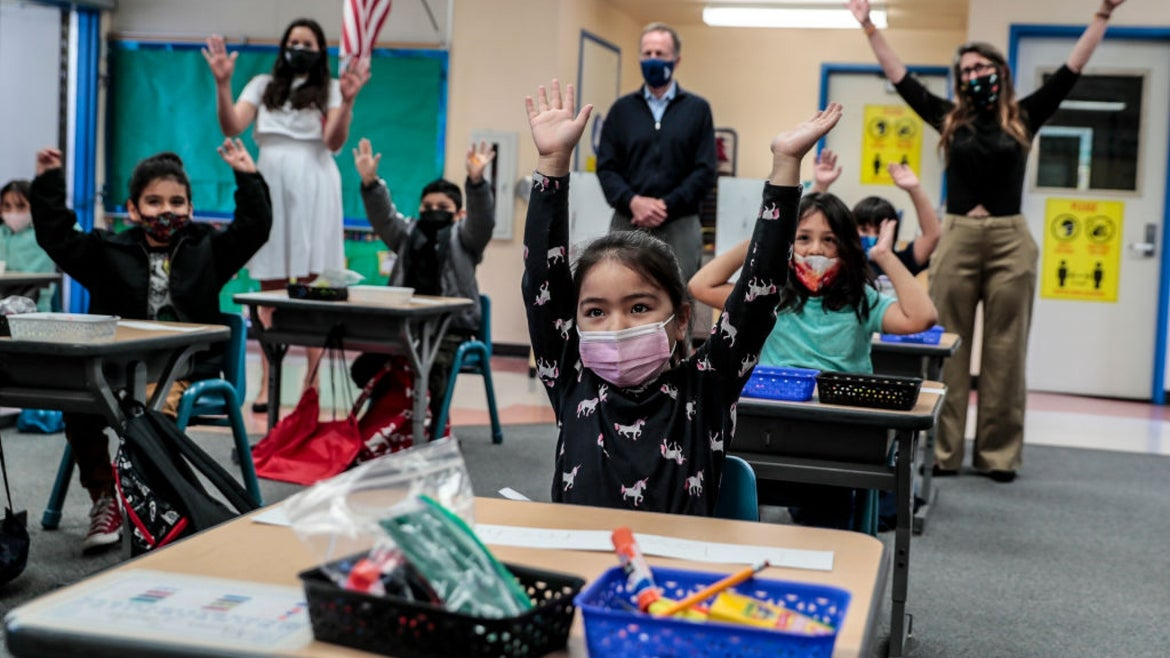 Group of excited masked kids in a kindergarten classroom with their hands raised above their heads
