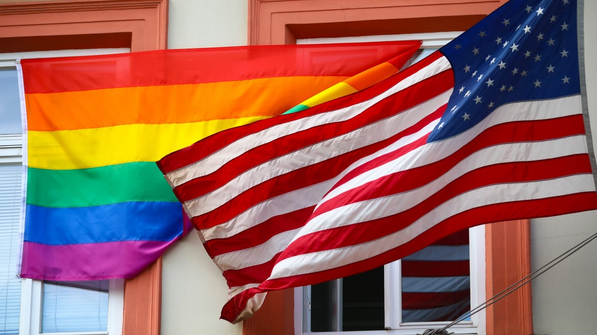Pride flag next to the American Flag in front of building