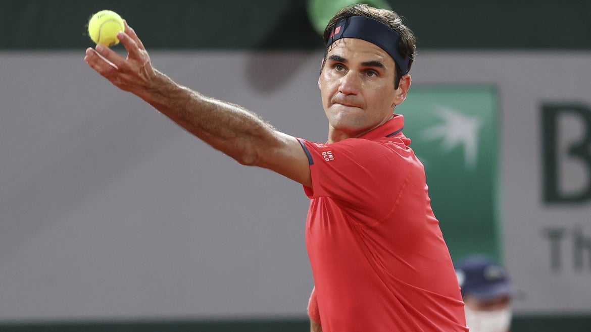 Federer in red shirt on court, holding tennis ball