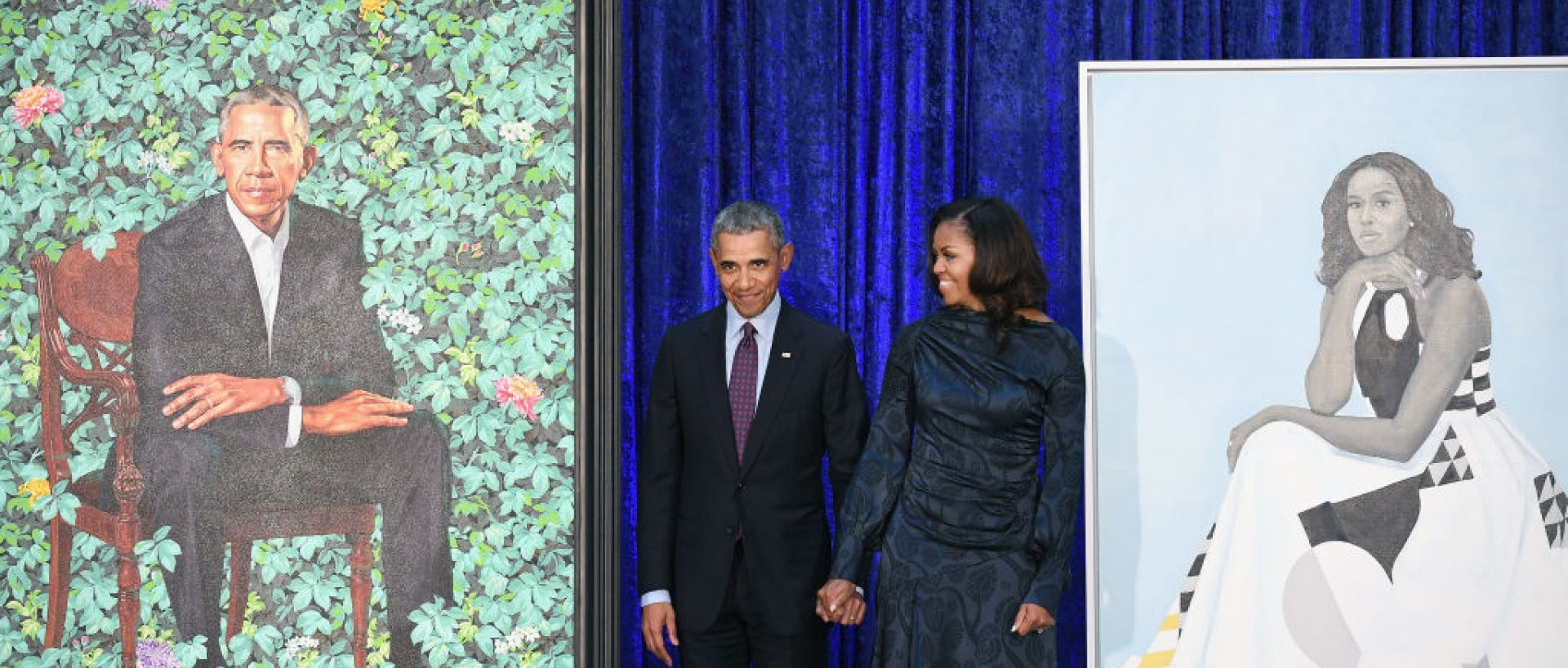 The Obamas standing in the middle of the portraits