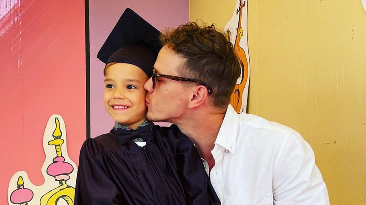 5-year-old Josey pictured in cap and gown with his father Ryan Dorsey kissing him on the cheek.