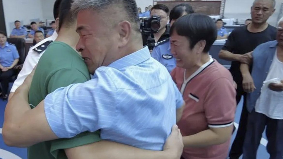 Guo Gangtang and his son Guo Xinzhen embrace at their reunion.