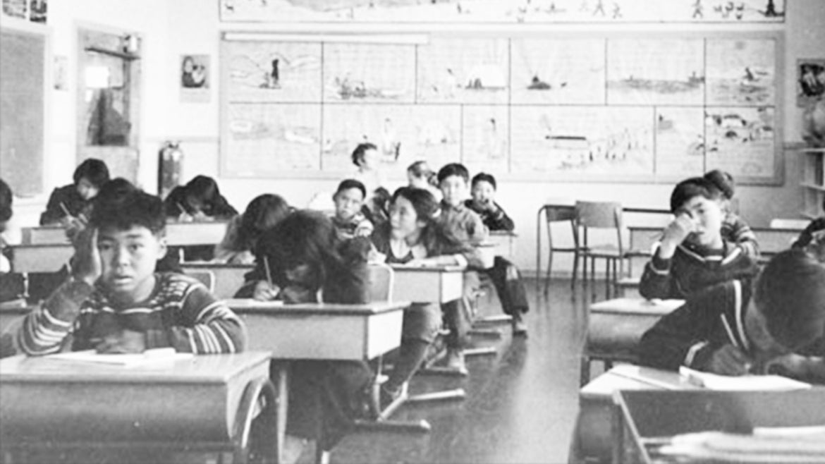 Young residential school students are photographed working at desks while at the Sir Joseph Bernier federal day school in Chesterfield Inlet, Nunavut.
