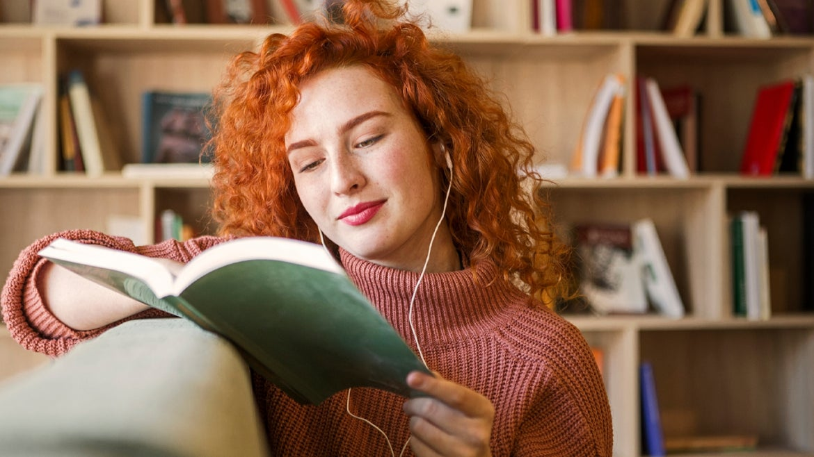 Happy young woman holding book reading