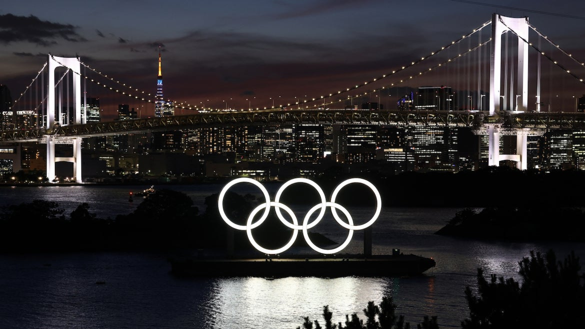 Olympic rings with the Rainbow Bridge in the background at the Odaiba Marine Park.