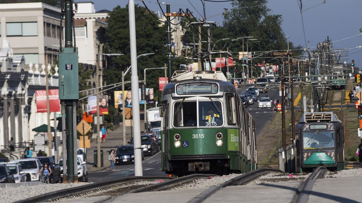 Automobile traffic and an MBTA Green Line train move along the Commonwealth Avenue Bridge in Boston as it reopens to traffic on Aug. 16, 2017.