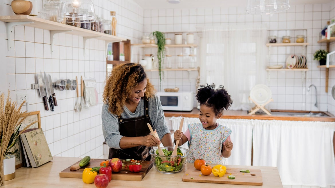 Mother and daughter cooking a meal in a kitchen.