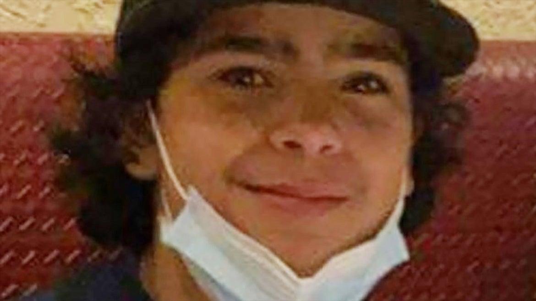Max Mendoza wearing a mask under his chin and a baseball cap
