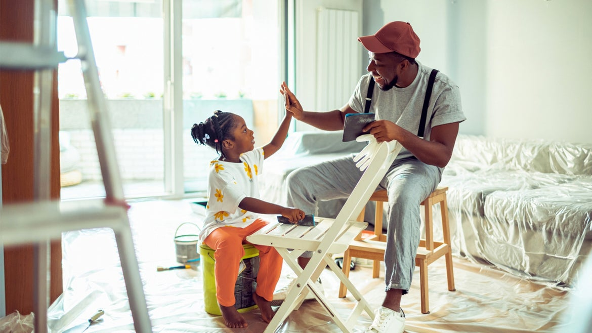 Close up of a father and his daughter painting a chair