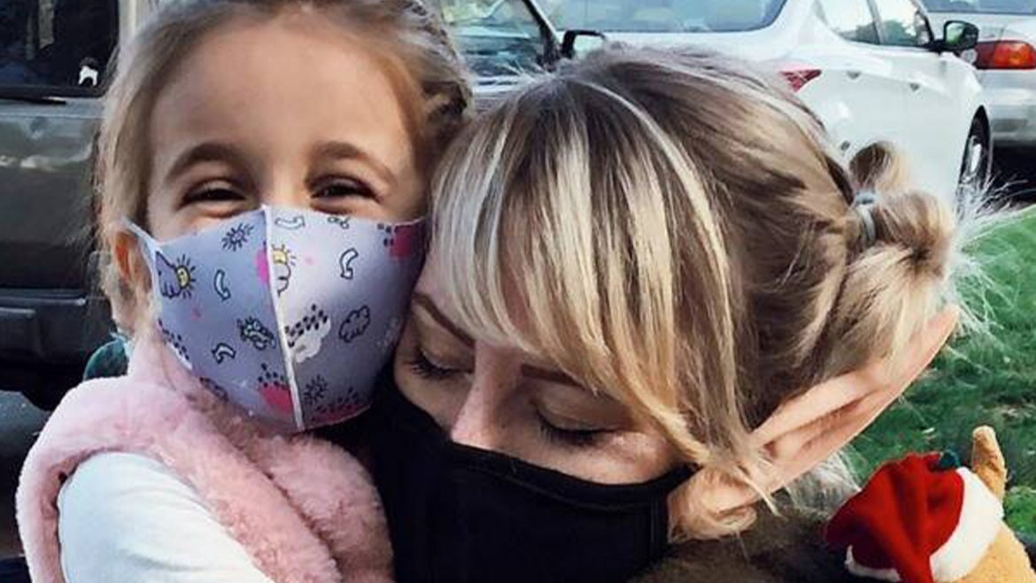 Kelly Kenney and Eliana pictured together in masks hugging