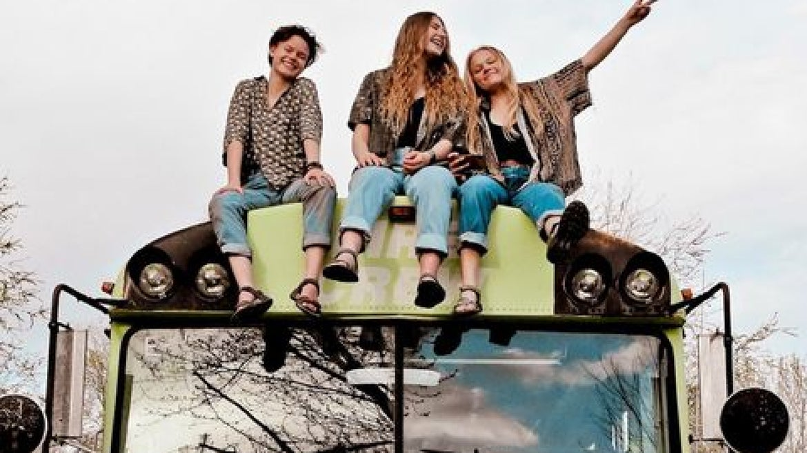 Three young woman sitting ontop of the green bus they renovated