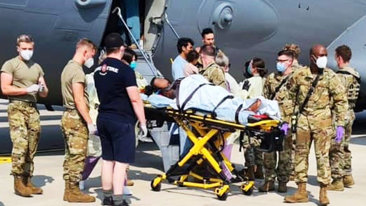 The pregnant woman is seen being helped off the plane by U.S. Airmen.