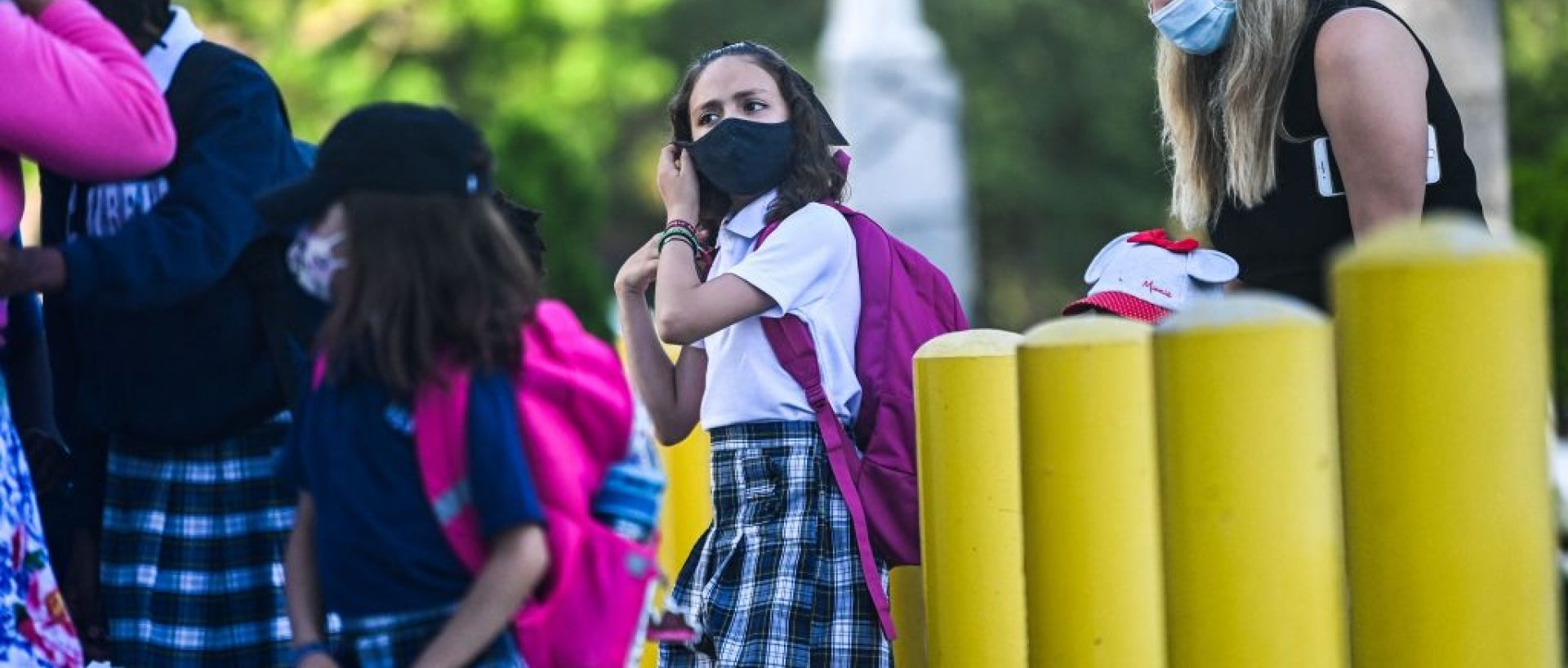 Children outside in uniforms and masks