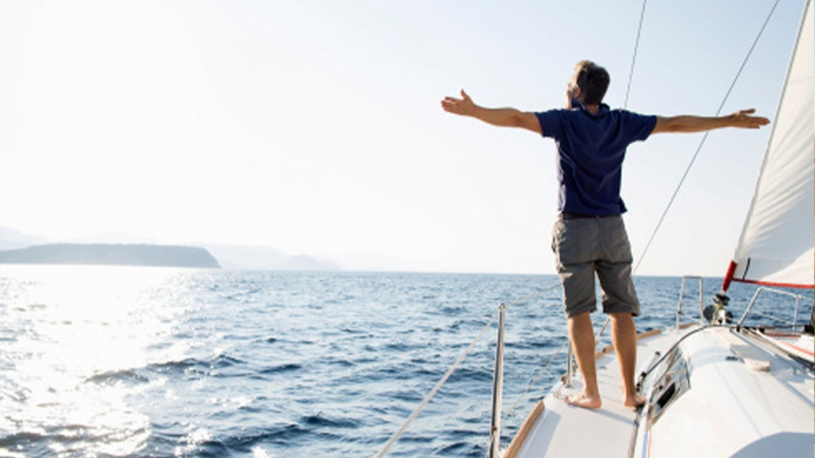 A stock image of a man enjoying himself on a boat in the ocean.