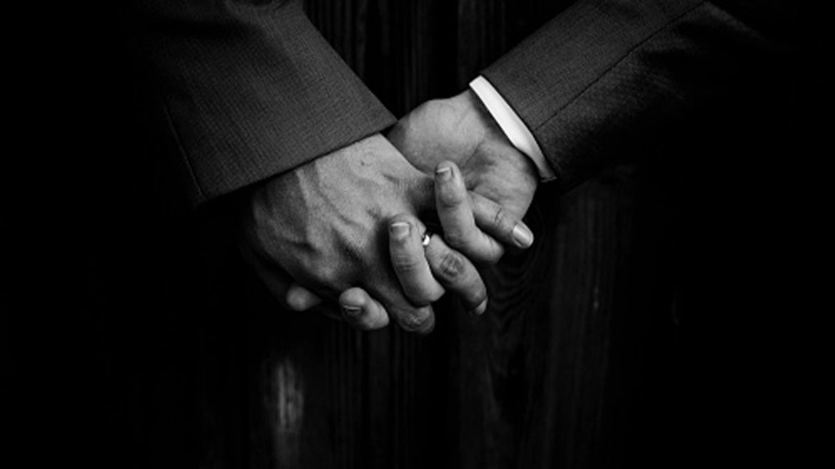 A stock image of a gay couple holding hands.