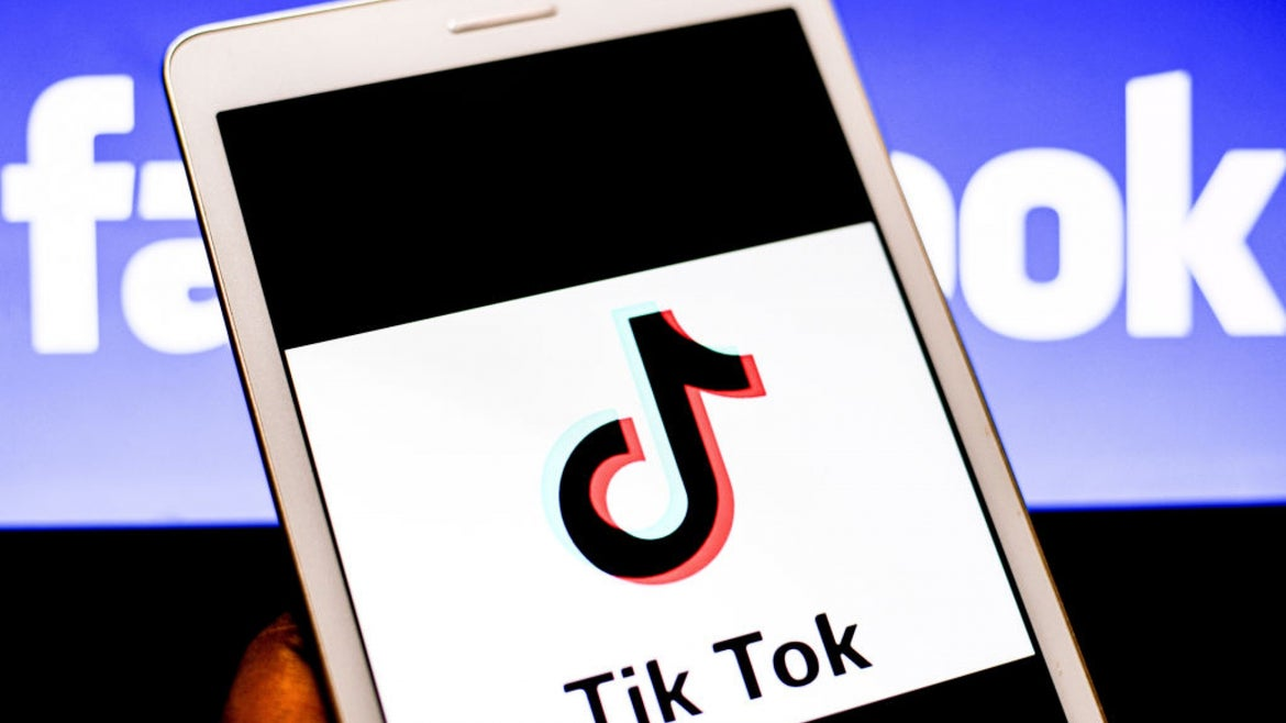 Tiktok logo on the screen of a phone being held by a hand, the facebook logo in the background