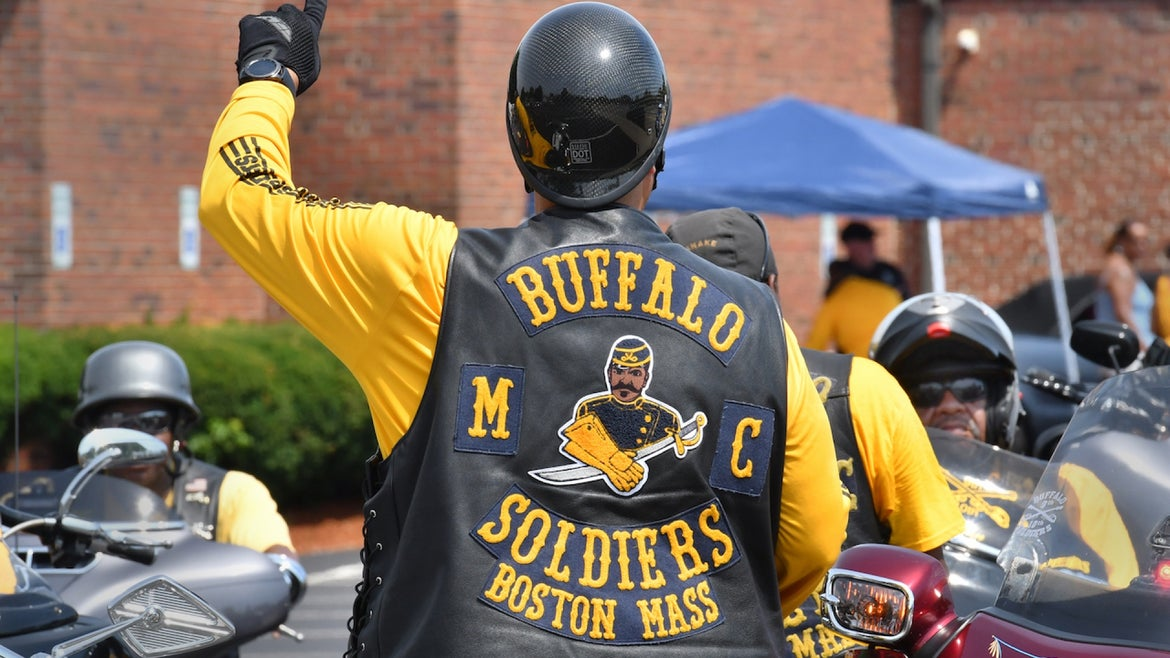 """A member of the Buffalo Soldiers Motorcycle Club signals the riders to prepare for the 11th Annual """"Buddy Run""""l, benefiting the SPARK Center at Boston Medical Center."""