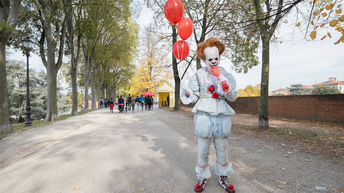 """A cosplayer dressed as Pennywise the clown from """"It"""" poses during the opening of the Lucca Comics and Games Heroes on November 2, 2017 in Lucca, Italy"""