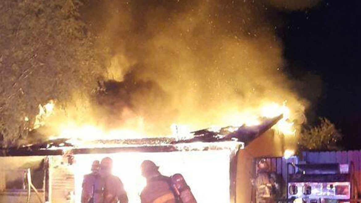 Firefighters standing in front of house in flames