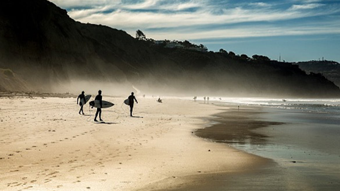 A stock image of surfers on a California beach.